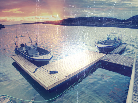 Hipster filter.  Fishing boat with fishing rods floating at shore, evening colorful  sea. 免版税图像