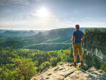 Man on a stone observing the landscape. Lonely young sportsman stands on the mountain and looks into the distance
