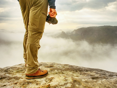 Hiker with camera in hands. Photographer takes fall photos with digital camera on peak above misty autumn landscape. Stockfoto