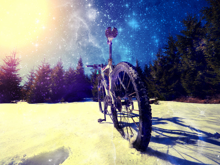 Wide view photo of mountain bike in deep snow. Winter trip in mountains. Hipster filter. Stock Photo