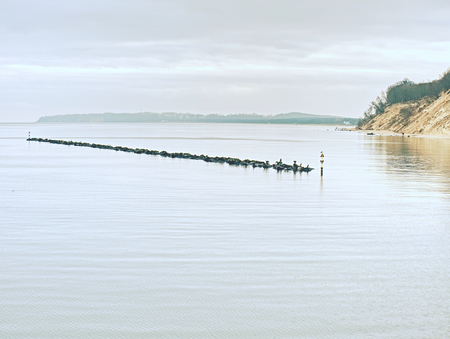 Timber groynes on the beach at the north sea. Moody blue sea Standard-Bild - 112919243