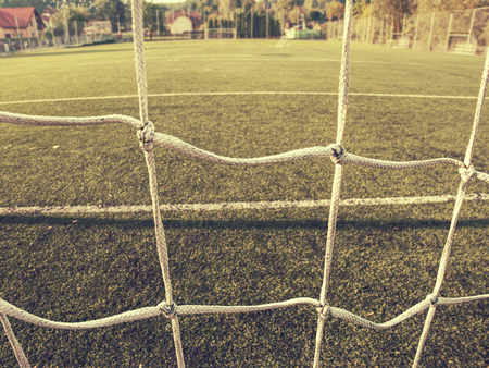 Soccer or football corner lines through safety net. View from behind the tribune net with blurred stadium and field pitch
