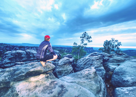 Alone tourist with baseball cap sporty clothes stand on cliff edge and watching into deep valley bellow. Cloudy sky and early fall weather.