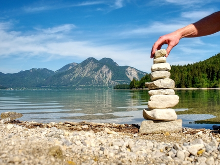 Stacked pebbles on the lake shore. Balanced stones stack at water with reflection