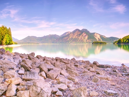 Pebble or rocky shore of the mountain lake, in the distance you can see the sharp Alps mountains