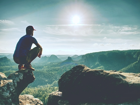 Sit on the edge. Man in blue yellow sports clothes  sit on sharp cliff and enjoying far view. View into misty hilly valley bellow