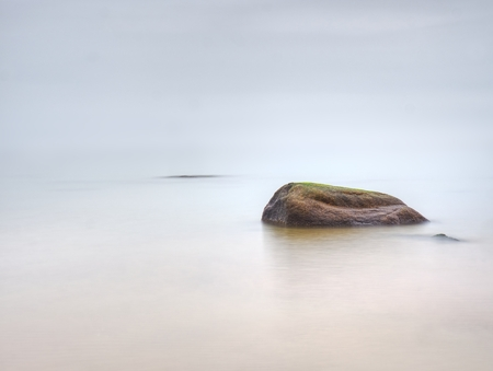 Rounded stoune stick out of shallow water of bay. Romantic walk along sea.