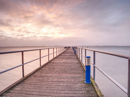 Empty dock, calm sea and sky background. View of wooden bridge above smooth ocean. Perspective of wooden pier in dock Archivio Fotografico