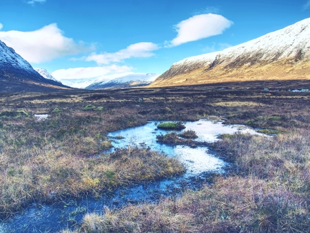 Rounded mountains peak against to cold river. Scotland highlands landscape within early spring. Banque d'images