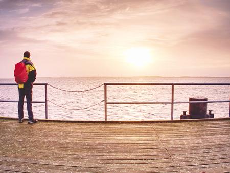 Man turtle in autumn mist on wooden pier over the sea. Depression dark atmosphere. Stok Fotoğraf