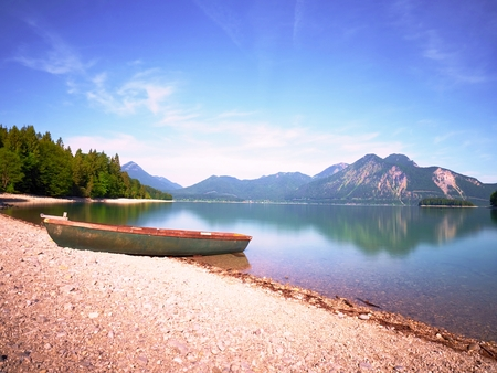 Modern sport fishing paddle boat anchored on shore of the lake bay. Peaceful level of lake. Windless sunny day. Banque d'images