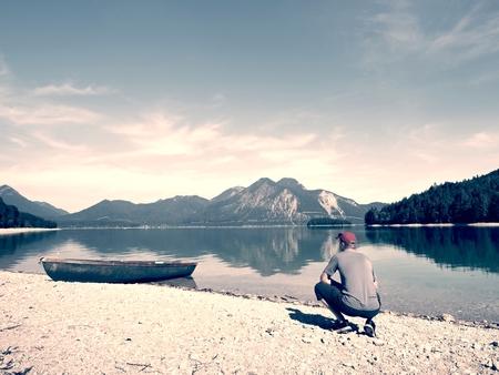 Sports boats, blue green mountain lake, windless summer day.