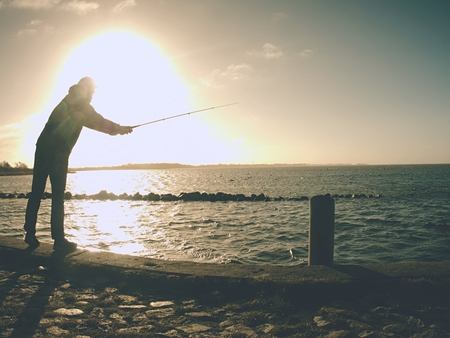 Fisherman with hat on the sea mole  with fish rod. Man standing above sea water and  fishing at sunset Stockfoto