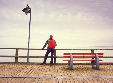 Pensive guy in trekking suit  on a wooden pier above the water.  Tourist at dusk on the docks bridge and looks afar. 版權商用圖片