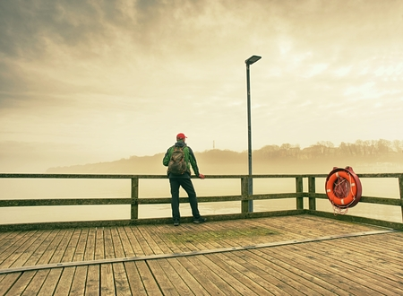 Man dreaming sitting on a wooden pier near the water and looking at far horizon