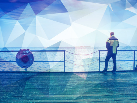 Abstract, over filtered. Tourist sit on a steel bench on a mole and take a break. Alone man enjoying misty morning at sea. Smooth water level. Stockfoto