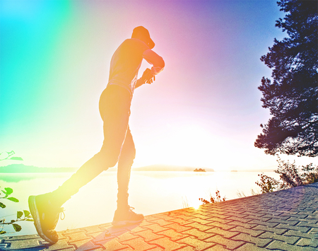 Abstract, over filtered. Sports man stretching body after running workout outdoors on beach at sunset 版權商用圖片