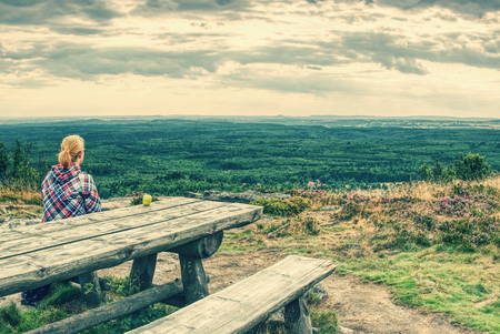 Young smiling blond girl trekker resting at wooden table with amazing view into landscape. Tired hiker sitting down and taking a break from hike. Фото со стока