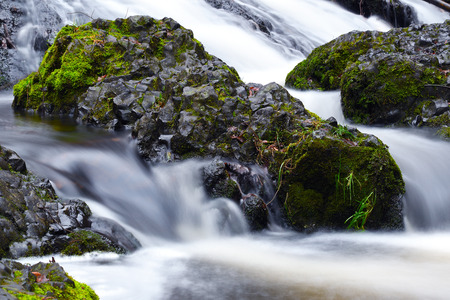 Basalt stone and colorful leaves below waterfall in autumn. Shinning bubbles in dark cold water
