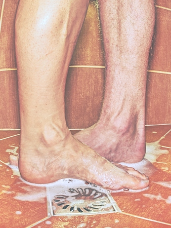 Two lovers, man and woman barefoot in shower.  Feet on red tilles selective focus on toes Imagens