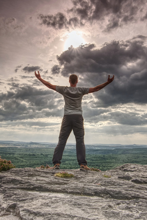 Silhouette of Person in hiking clothing with raised arms and spread making embrace the world gesture staying on edge