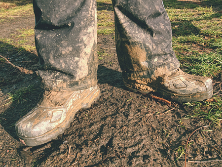 Farmer wearing muddy boots in daily business. Muddy rubber boot in horse farm area