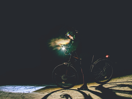 MTB cyclist stop the Bike on frozen lake in the Night and check the paper map. Extreme orienteering bike race