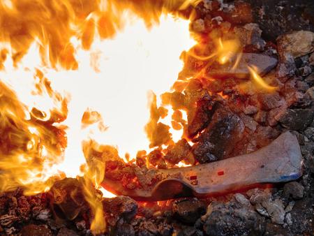 Blacksmith working hard  with iron and fire to make horseshoe