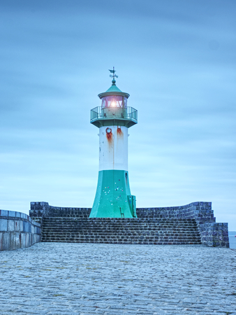 Shinning lighthouse at the end of stony pier. Cloudy eveningafter rainy day, Sassnitz, Germany