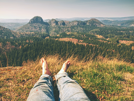 Tired hikers legs without shoes. Traveler relaxing with mountains view on background