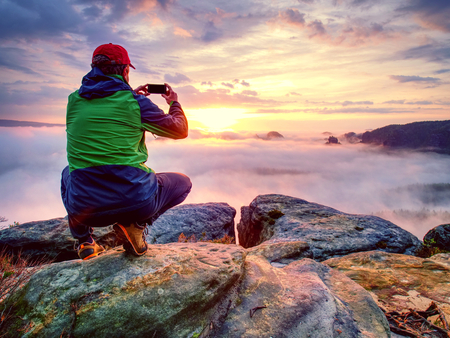 Man taking picture of amazing fall mountains on his phone in misty weather