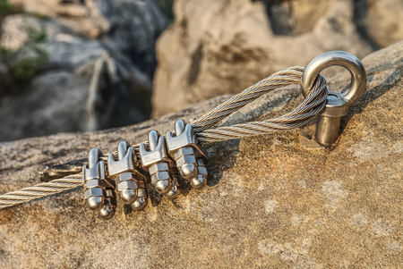 Mountain iron anchor for free climbing. Stainless cable fixed to the rock for the safety of the walking route in the mountains