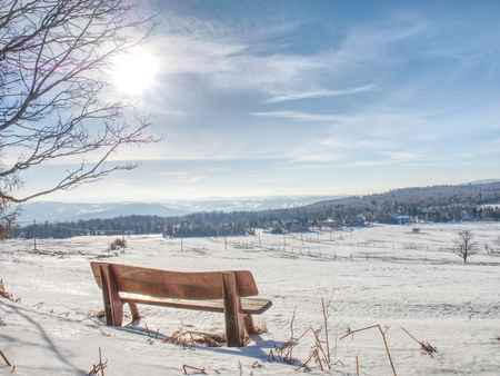 Winter landscape, sunny day. Footprints in the fresh snow lead to a wooden bench