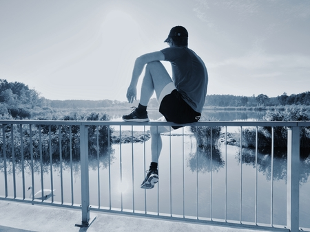 Single Man in sport clothing sit on bridge handrail and watch over lake to Sun