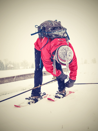 Nice woman on a winter adventure trip on snowshoes. Fresh powder snow is falling from dark sky.