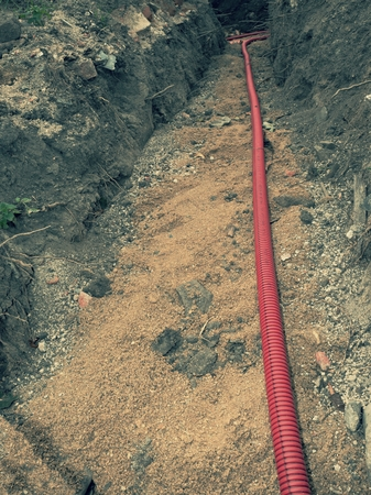 Excavation at road construction. Modern plastic water, electric and gass flexible tubes. Archivio Fotografico