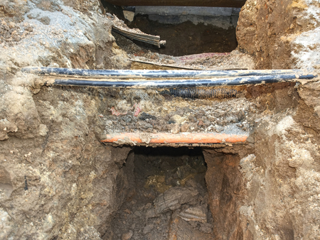 Building of lines of metallic and fiber optic cables of communication network connection. The trench carries the conduits for gas water electric sewage and phone services