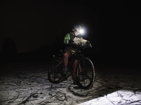 Outdoor orienteering extreme bike race. Woman check the map. Kind of sports that require navigational skills using a map and compass to achieve target. Banco de Imagens