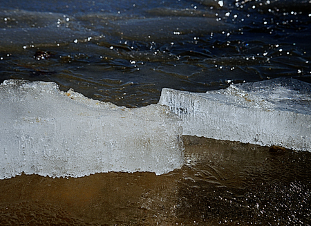 Frozen bubbles in drifting floe. Arctic ice cough on sandy beach slowly melting under hot sun. Climatic changes.