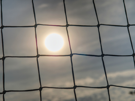 Soccer gate with sunset background. Detail of tennis net on court 免版税图像