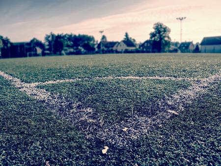 White stripe on artificial green soccer field. Yellow leaves fallen on green football soccer grass field. End of outside season.