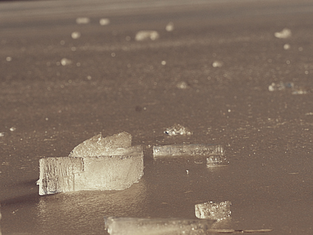 Frozen broken ice. Abstract ice floe image with Sun reflection in deep cracks and bubbles .
