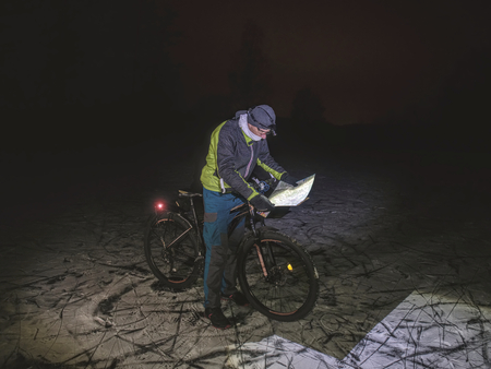 Biker lost path in night snowdrift. Man with mountain bike stay in powder snow and check map.