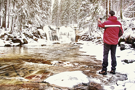 Nature photographer takes picture of winter snow landscape set in woodland with waterfall