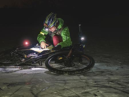 Sports woman is taking part in trail biking race outdoor in winter night. Woman joint night orienteering extreme bike race.