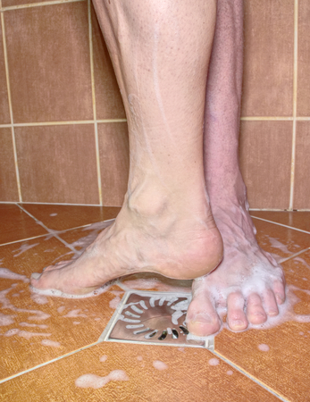 Adult lovers playing with foot in shower room. Nice moment of together living couple
