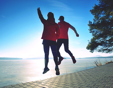 Flying jumping bodies of woman and man bodies at lake. Sports people within morning workout in sunny spring day. Condition excercise