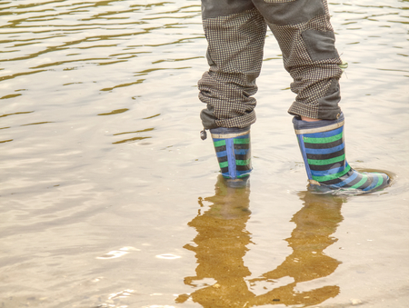 Floody river. Muddy brown water of rised river. Child wearing striped rain boots into a puddle. Close up. Kid having fun with splashing with water