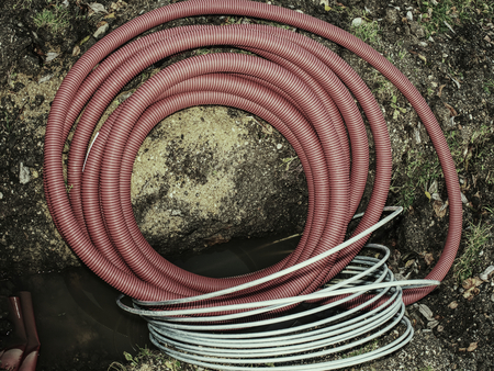 Electric wires in flexible protective tubes with protective red foil. Building of electric lines in trench.
