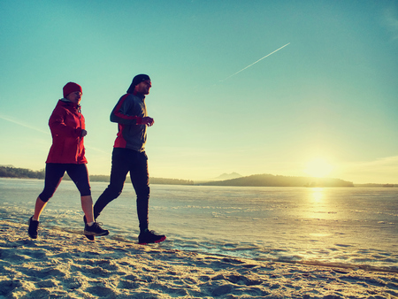 Sports and  Fitness. Fit person running at shore, workout jogging theme at  winter beach.